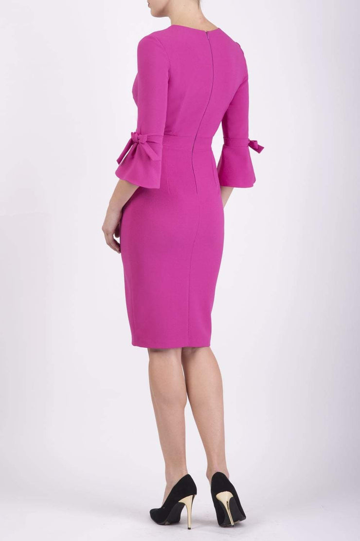blonde model wearing diva catwalk zoe 3 4 sleeve formal dress with a split rounded neckline and split on skirt in pink colour back