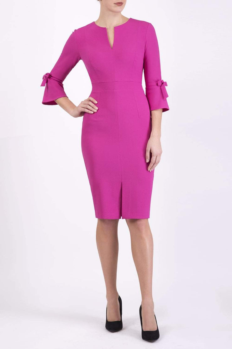 blonde model wearing diva catwalk zoe 3 4 sleeve formal dress with a split rounded neckline and split on skirt in pink colour front