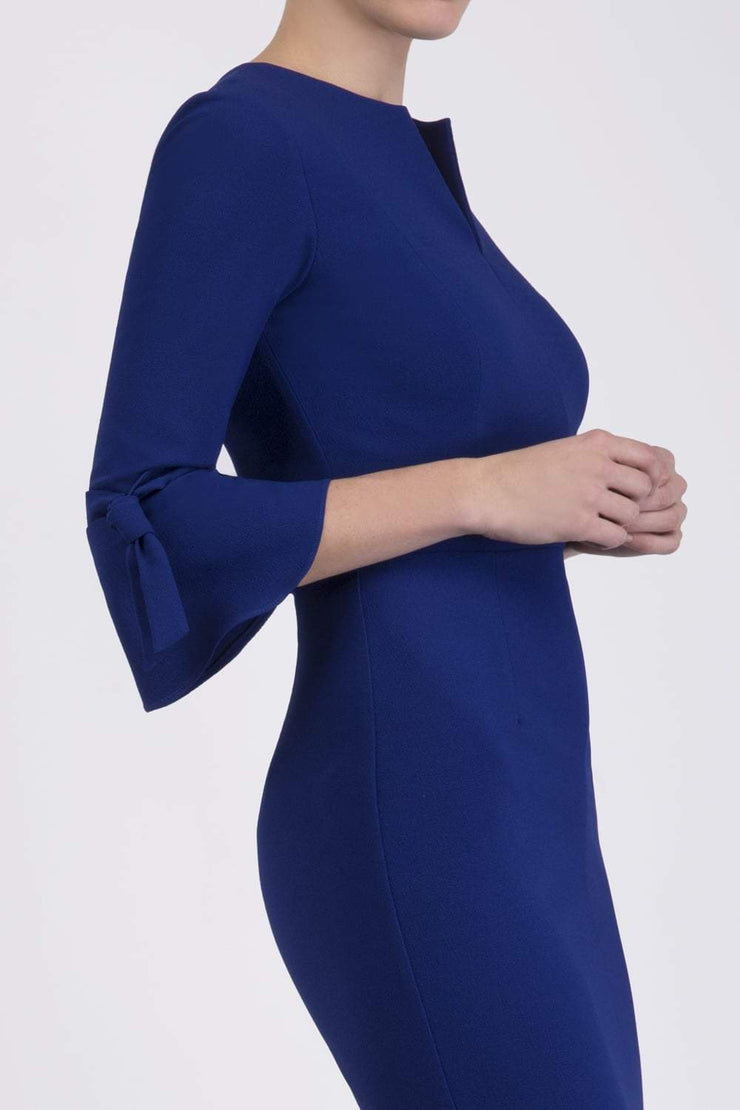 blonde model wearing diva catwalk zoe 3 4 sleeve formal dress with a split rounded neckline and split on skirt in oxford blue colour front