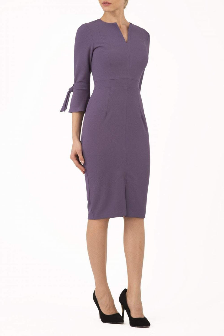 blonde model wearing diva catwalk zoe 3 4 sleeve formal dress with a split rounded neckline and split on skirt in opulent mauve front
