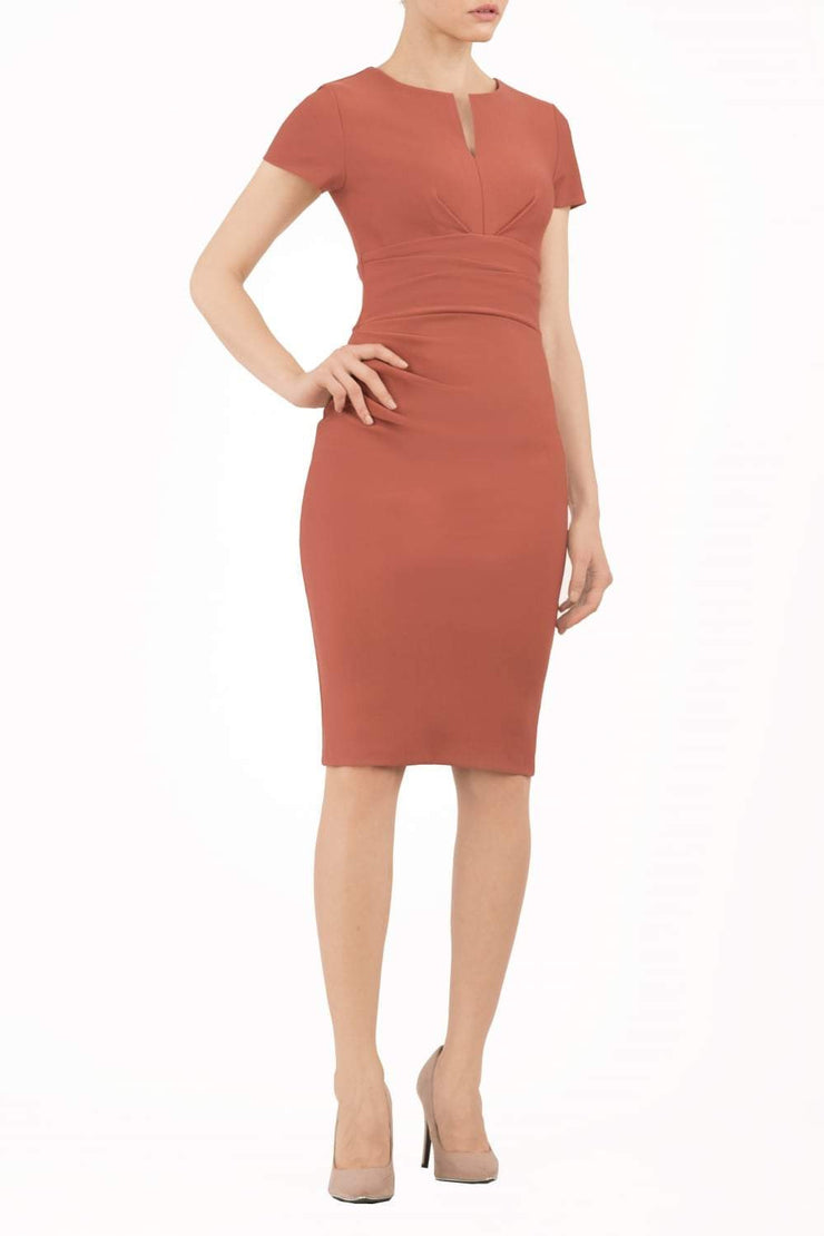 Model wearing Diva Catwalk Donna Short Sleeve Pencil Dress with a wide band and pleating across the tummy area in Marsala Brown  front