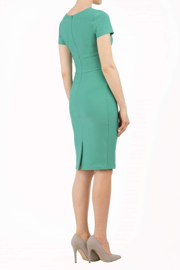 Model wearing Diva Catwalk Donna Short Sleeve Pencil Dress with a wide band and pleating across the tummy area in Emerald Green back