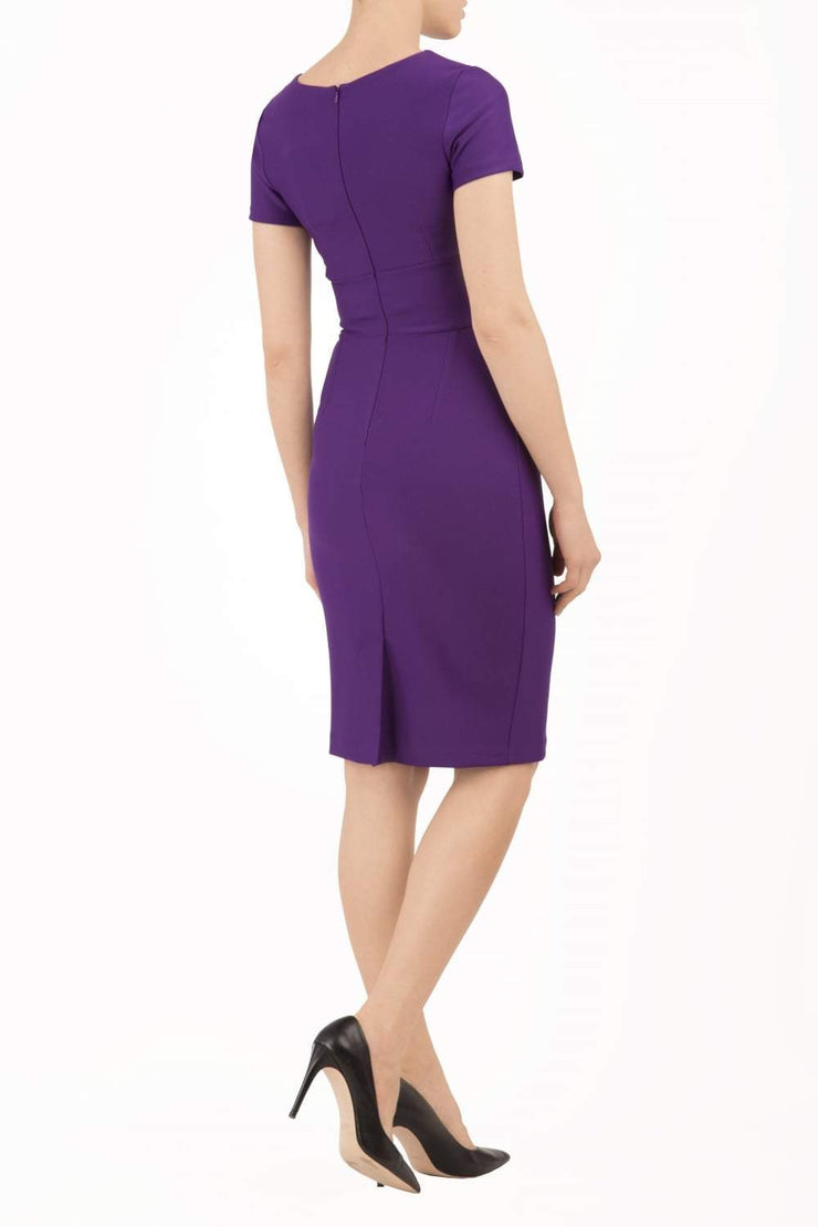 Model wearing Diva Catwalk Donna Short Sleeve Pencil Dress with a wide band and pleating across the tummy area in Royal Purple back