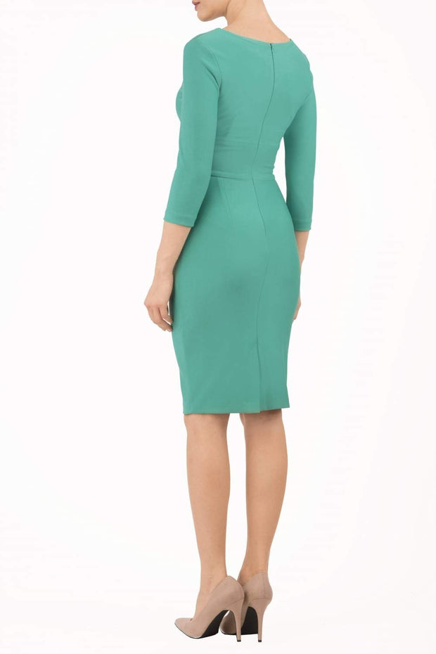 model wearing diva catwalk donna pencil dress in green colour with wide band and sleeves and rounded neckline with low split in front