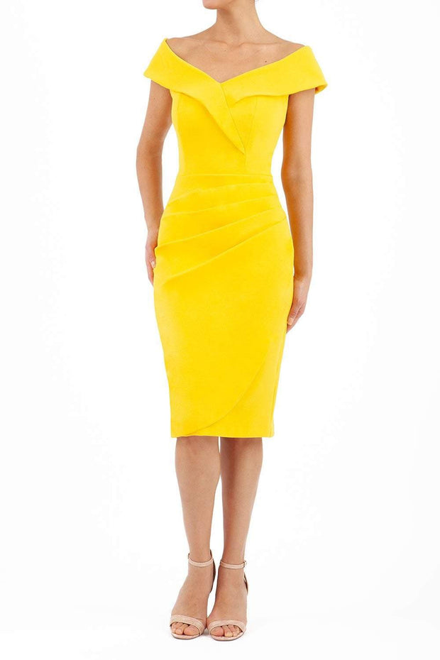 brunette model wearing diva catwalk evening pencil skirt dress sleeveless with lowered neckline and pleating on side in yellow colour front