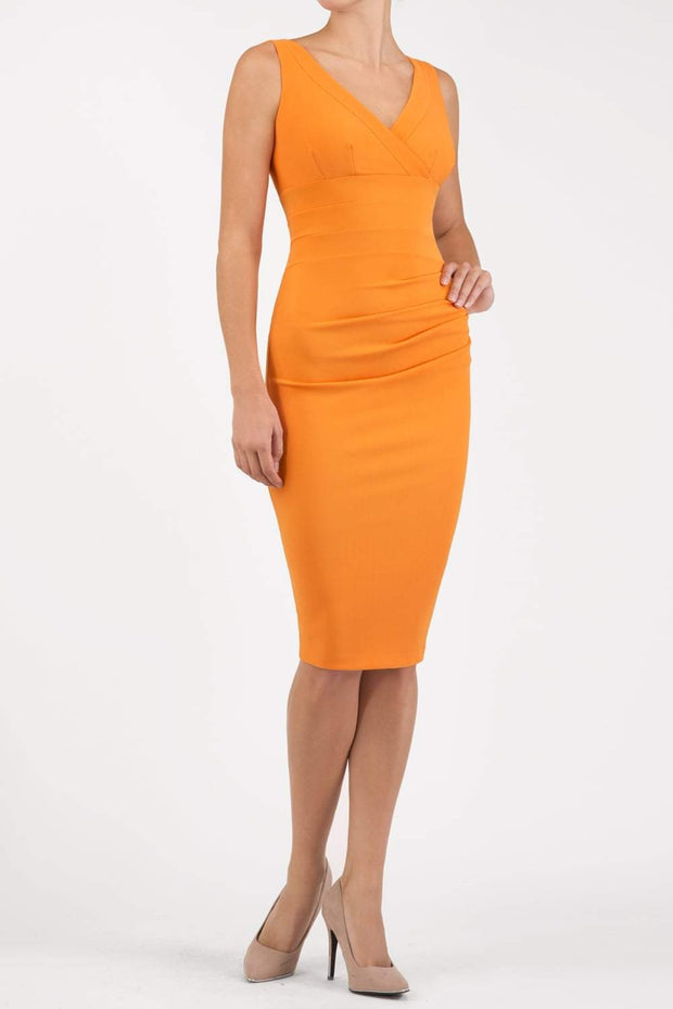 Model wearing the Diva Banbury gathered dress in bodycon pencil dress design in sun orange front image