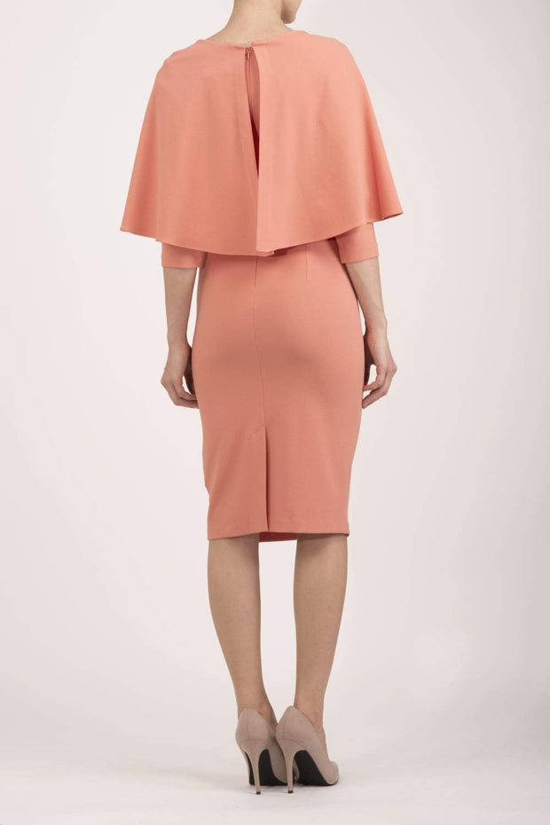 model wearing diva catwalk lizanne pencil-skirt dress with an attached wide cape detail and 3 4 sleeves in colour peach back