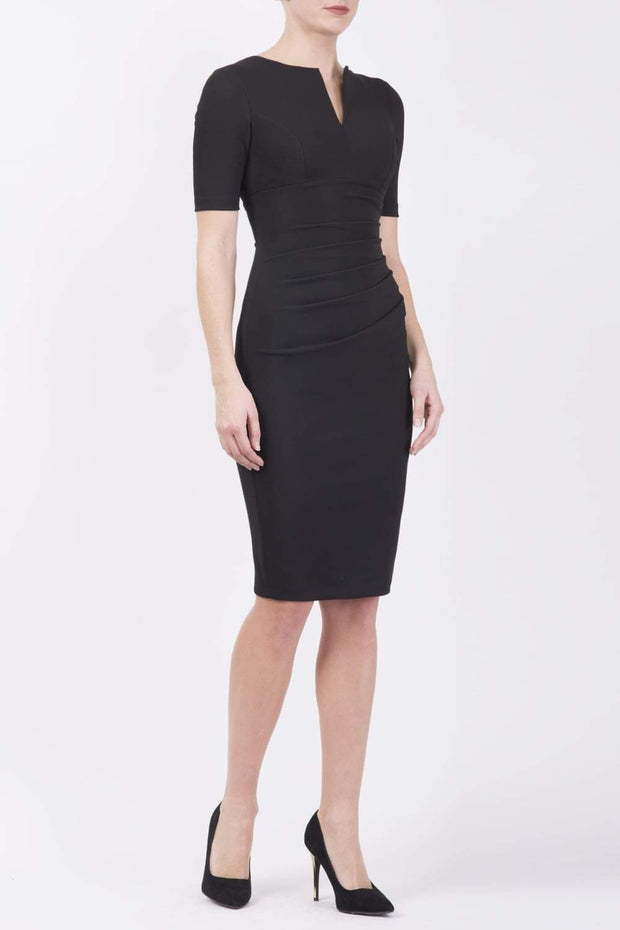 blonde model is wearing diva catwalk lydia short sleeve pencil fitted dress in black colour with rounded neckline with a slit in the middle front