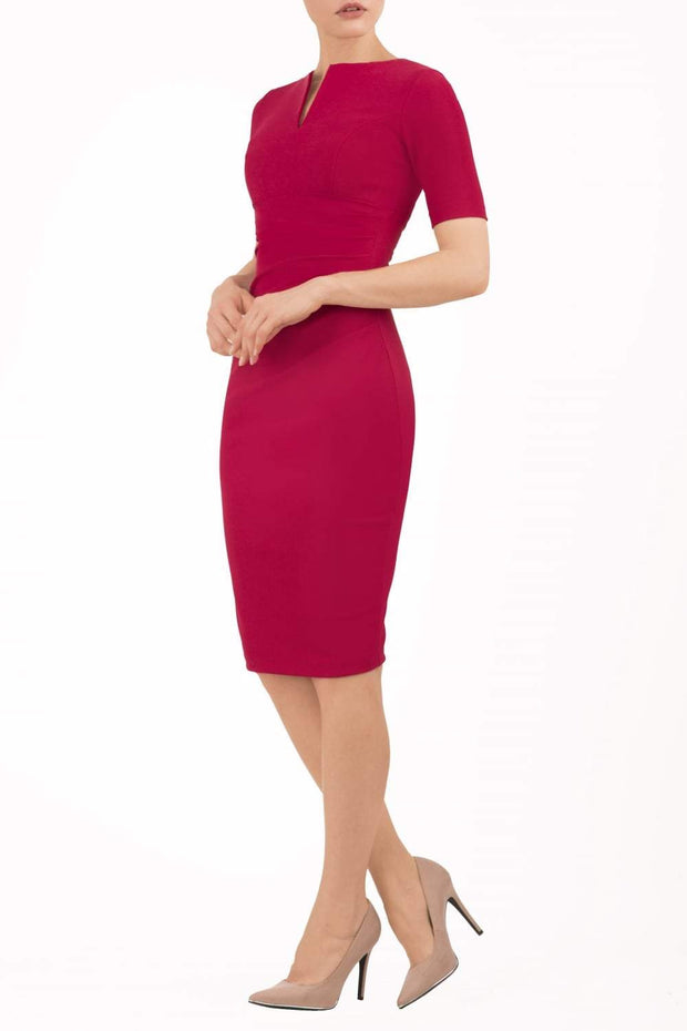 blonde model is wearing diva catwalk lydia short sleeve pencil fitted dress in red colour with rounded neckline with a slit in the middle front