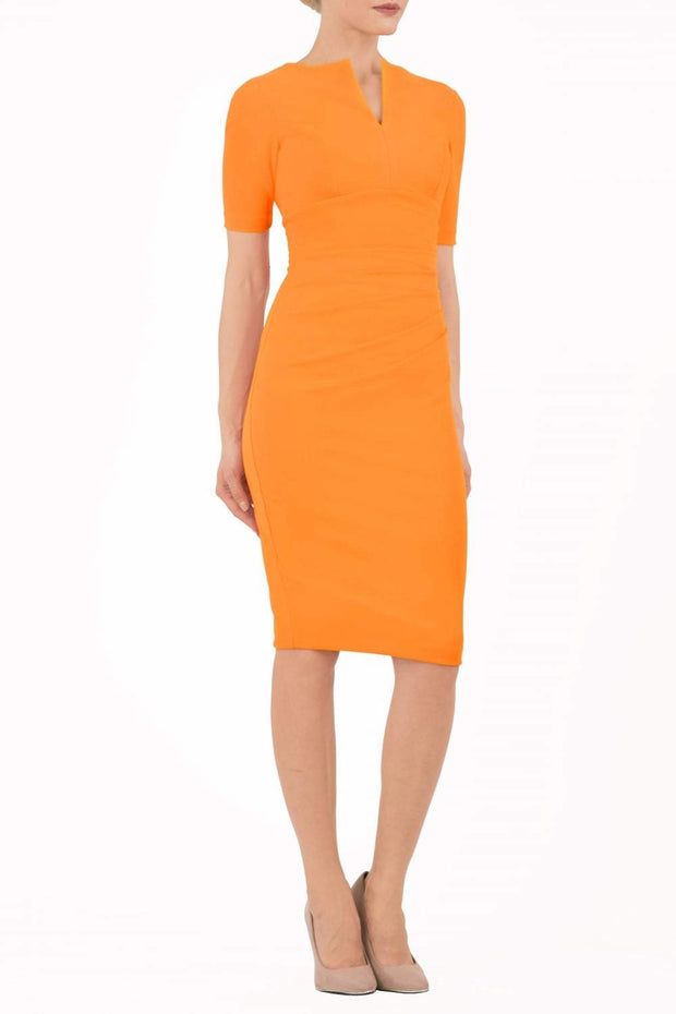 model is wearing diva catwalk lydia short sleeve pencil fitted dress in sun orange colour with rounded neckline with a slit in the middle back