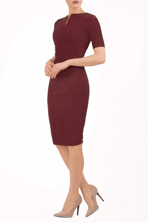 model is wearing diva catwalk lydia short sleeve pencil fitted dress in burgundy colour with rounded neckline with a slit in the middle back