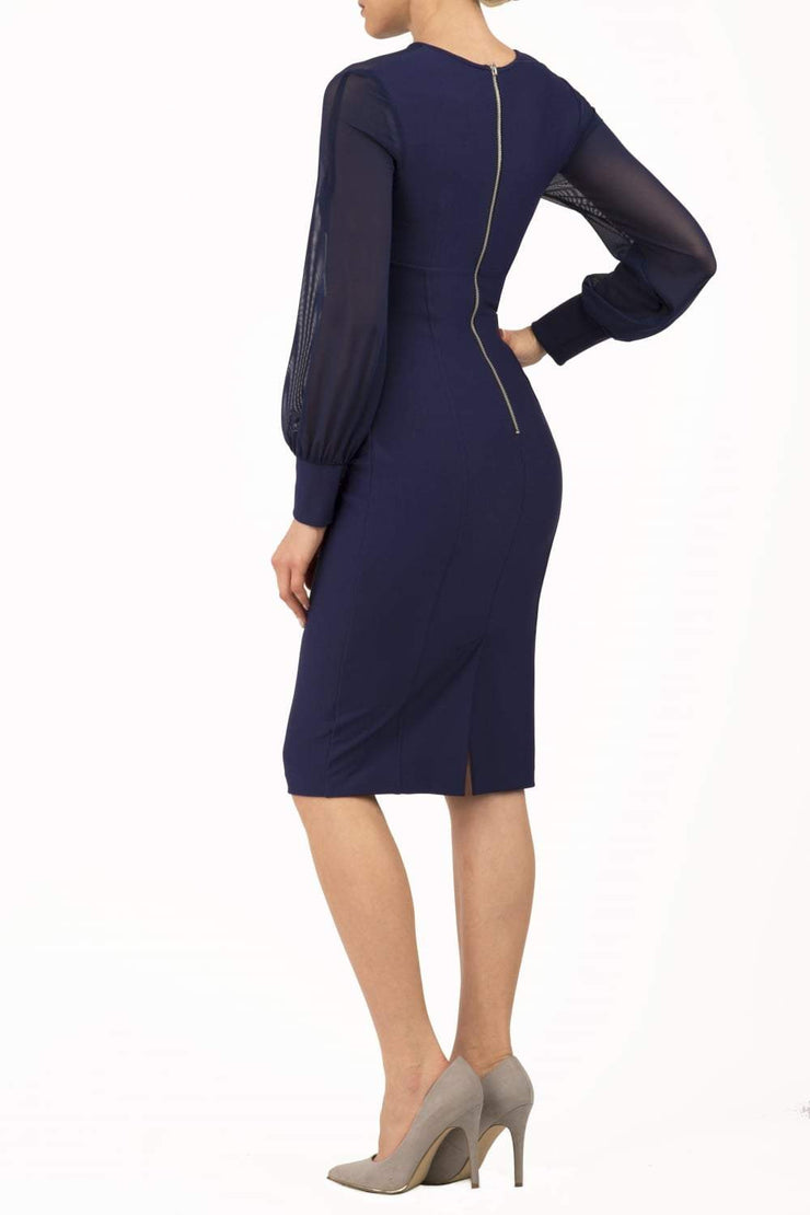 brunette model wearing diva catwalk navy pencil dress with long sleeves knee length and mesh detail sleeves back