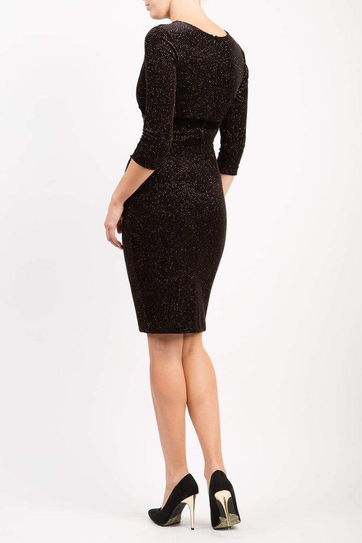 Brunette hair Model wearing 3/4 sleeve knee length glitter dress with velvet waistline