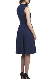 brunette model wearing diva catwalk oceana a-line swing skirt sleeveless dress with funnel neckline and tie detail in navy blue back