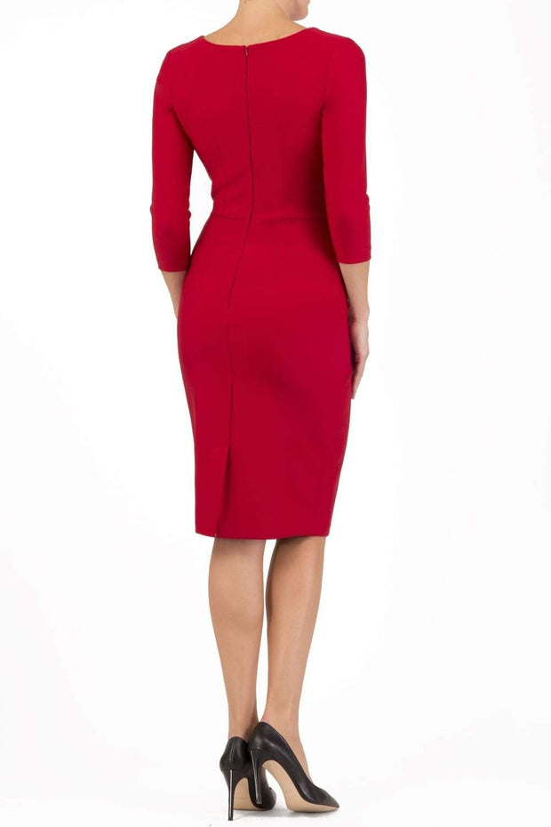 brunette model wearing diva catwalk couture althorp pencil fitted dress with sleeves and rounded neckline and bow detail at the top in cardinal red colour back
