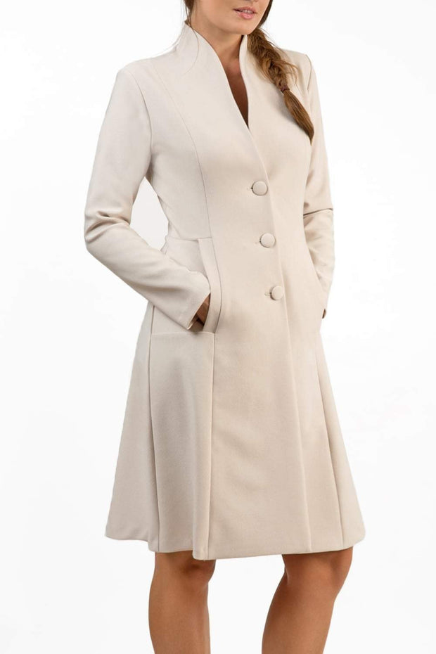 brunette model wearing diva catwalk couture fine raquella coat with buttons across the front and long sleeves with high neck and pockets in sandy cream colour front