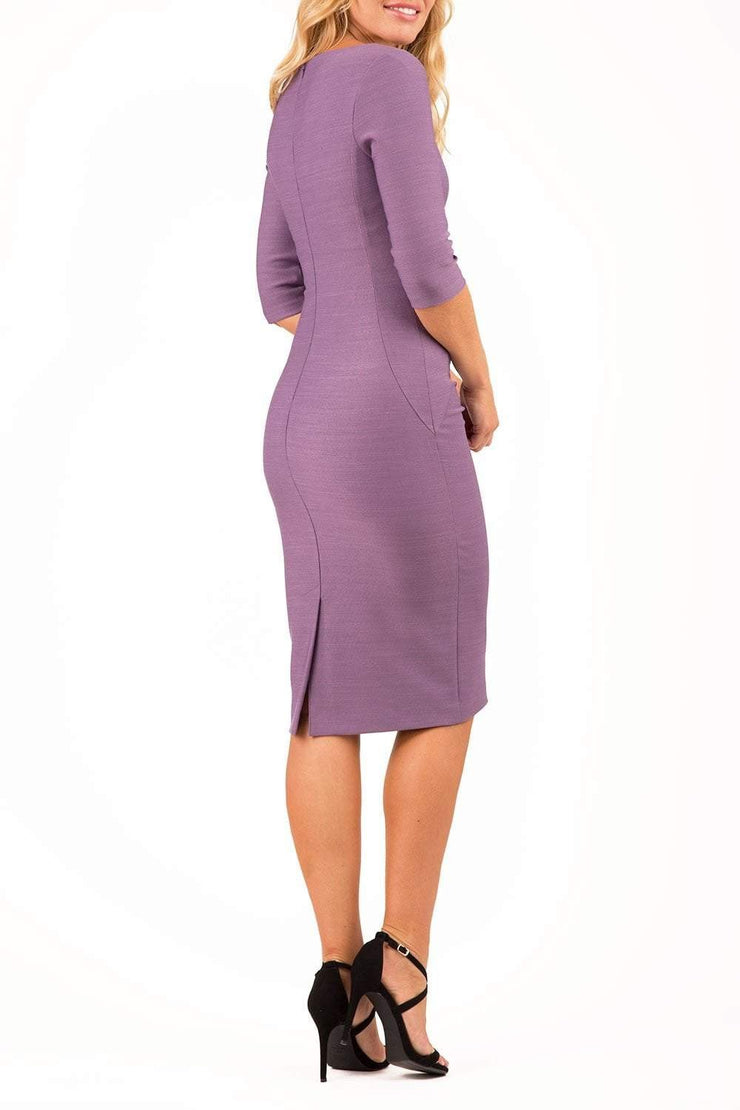 model wearing seed couture royale pencil skirt dress with pleating across the tummy area with rounded neckline with a split in the middle and 3 4 sleeve in lilac colour front