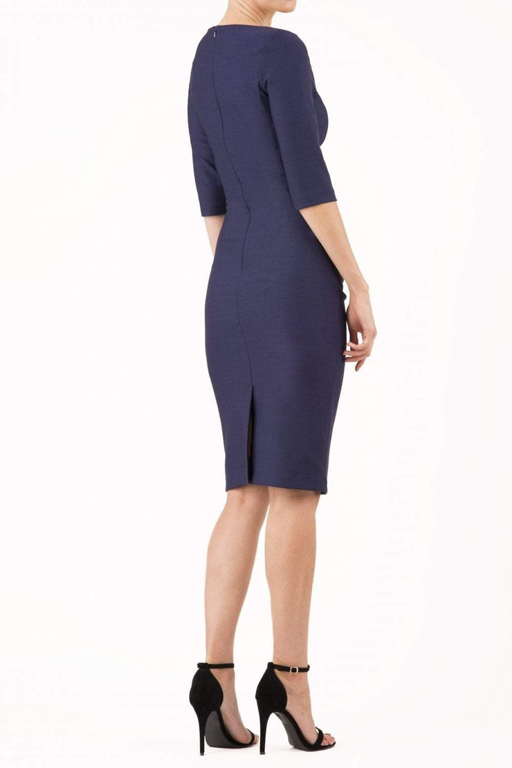 model wearing seed couture royale pencil skirt dress with pleating across the tummy area with rounded neckline with a split in the middle and 3 4 sleeve in navy blue colour back