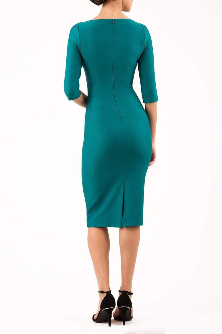 model wearing seed couture royale pencil skirt dress with pleating across the tummy area with rounded neckline with a split in the middle and 3 4 sleeve in green colour back