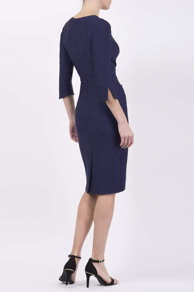 blonde model wearing seed tuscany pencil fitted dress in navy blue colour with a split in the neckline and split detail on sleeves back