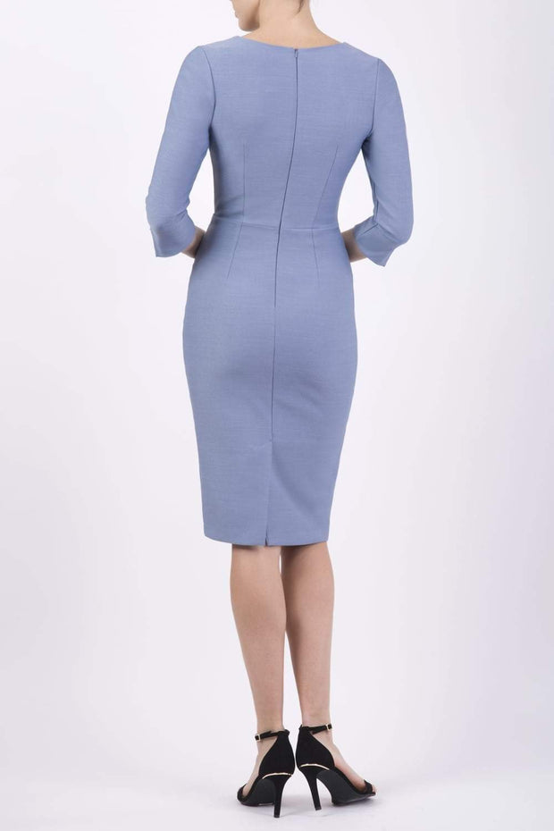 blonde model wearing seed tuscany pencil fitted dress in steel blue colour with a split in the neckline and split detail on sleeves back
