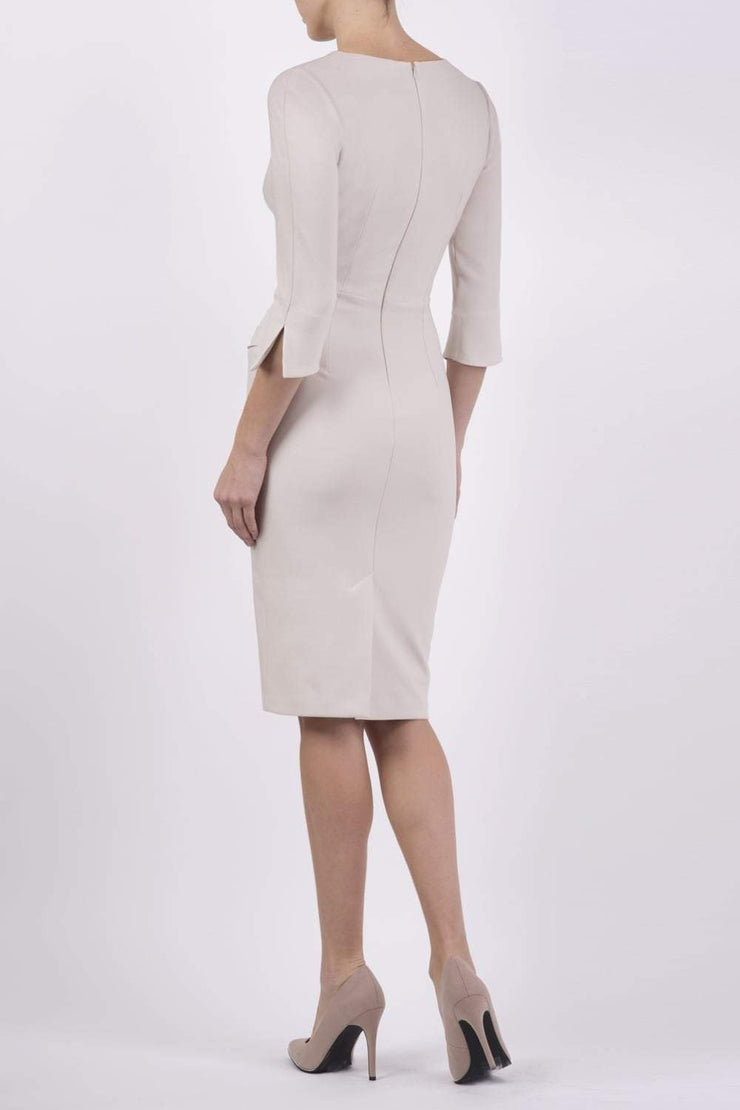 blonde model wearing seed tuscany pencil fitted dress in sandy cream colour with a split in the neckline and split detail on sleeves back