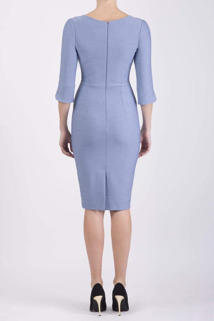 model wearing seed couture zara pencil skirt dress in pale blue with asymmetric neckline with sleeves back