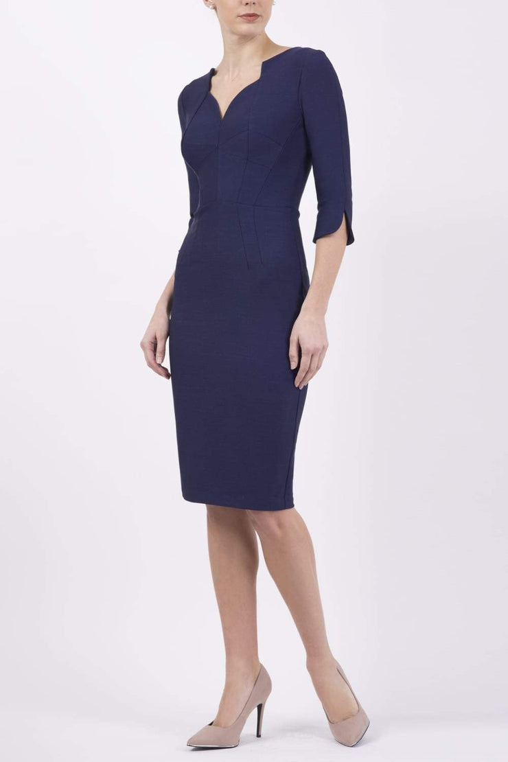 model wearing seed couture zara pencil skirt dress in navy with asymmetric neckline with sleeves front