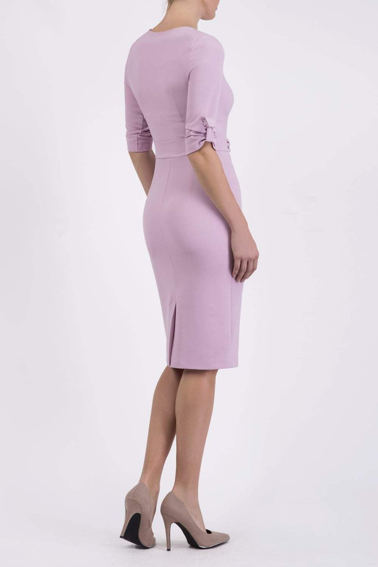 brunette model wearing diva catwalk tryst pencil pale pink dress with sleeves and belt detail at the front with rounded neckline back