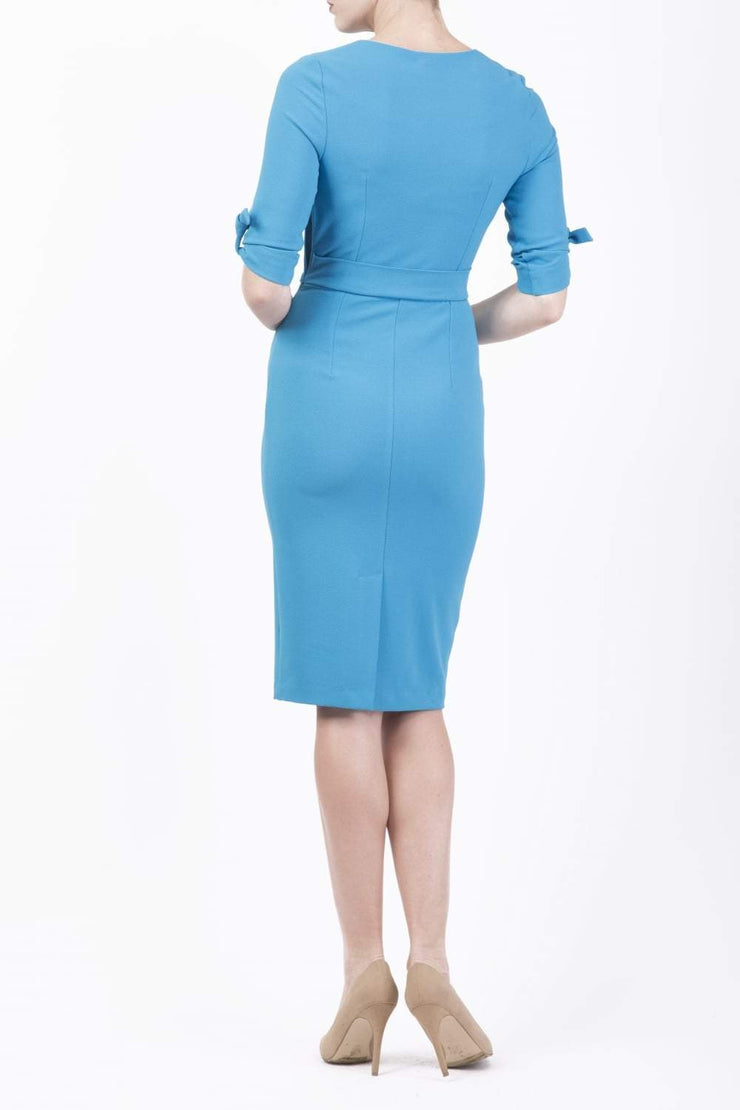 brunette model wearing diva catwalk tryst pencil blue dress with sleeves and belt detail at the front with rounded neckline back