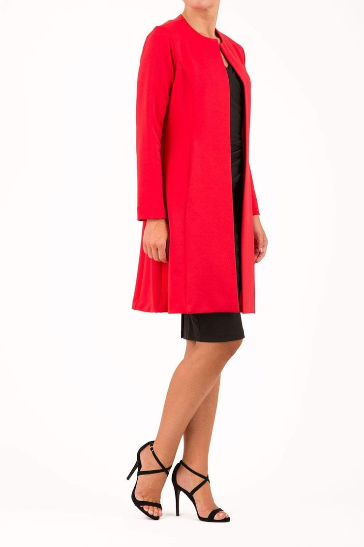 model wearing diva catwalk electric red coat with long sleeves and a belt front