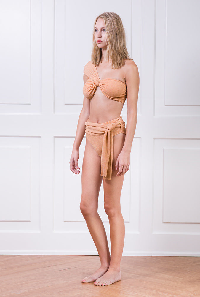 Peach metallic asymmetrical bikini top and high-waisted bikini bottom with belt