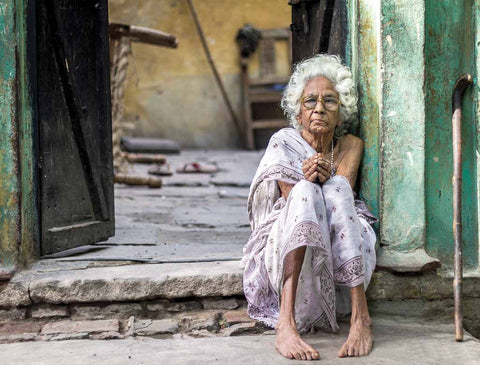 Older woman sitting on the porch. She has been abandoned.
