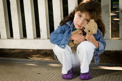 A young girl sitting outside holding a teddy bear.  She has been abandoned.