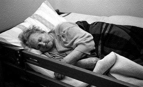 Elderly woman lying on a cot