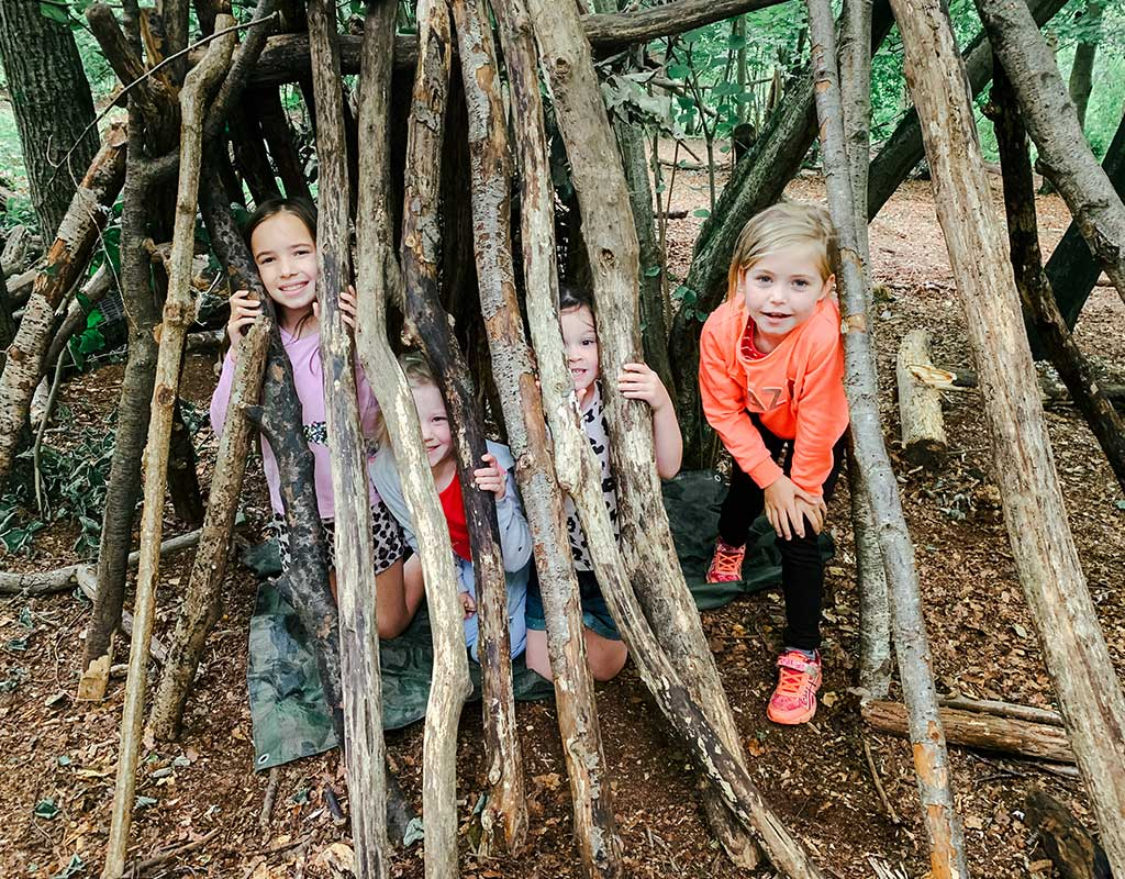 Group on young girls inside a den created from branches at Blackwood Forest, Hampshire