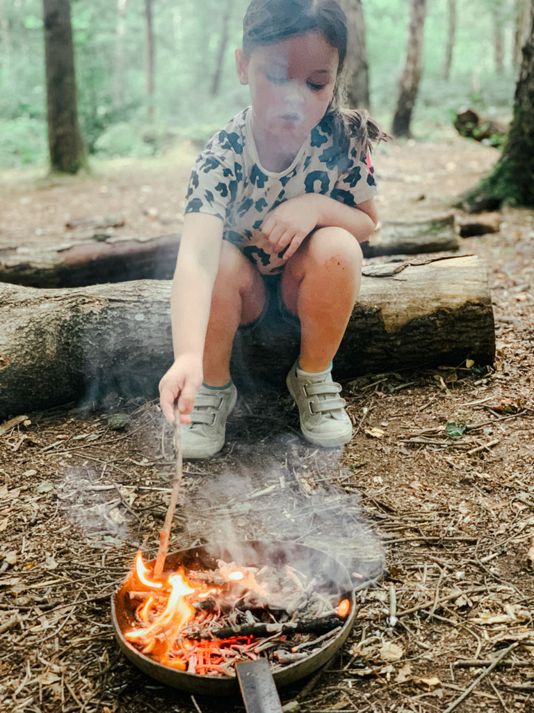 Young girl toasting a marshmallow over a fire at Blackwood Forest, Winchester, Hampshire