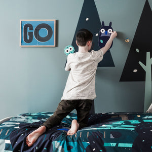 Young boy kneeling on Treetops bedding applying wall stickers to the wall. The blue wall has two wall stencilled trees painted and a framed Go explore poster print