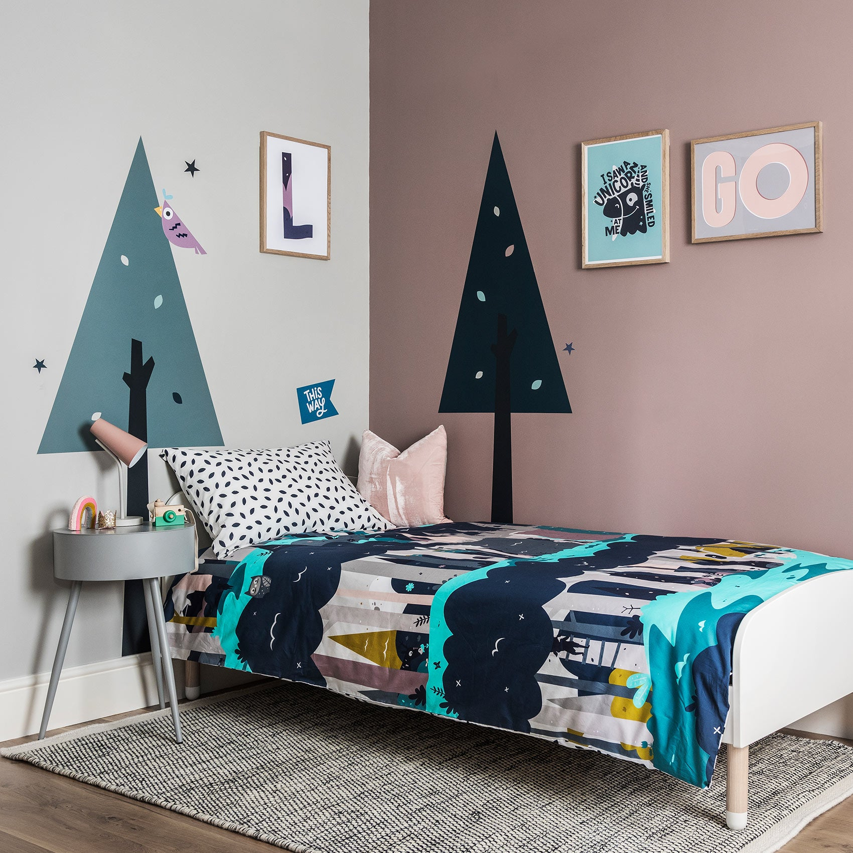 Enchanted Forest child's bedroom. Pink and Grey walls with wall stencil trees, poster prints line the walls with Enchanted Forest bedding made up on the bed.
