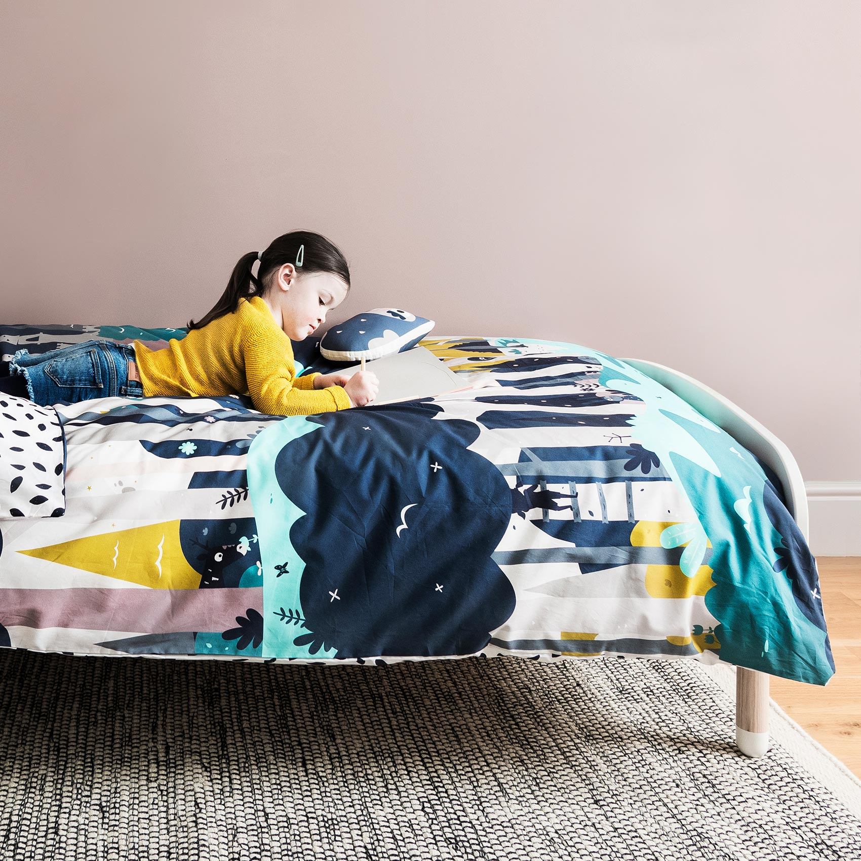 Young girl in a yellow top lying on her bed drawing on top of Pea Enchanted Forest bedding.