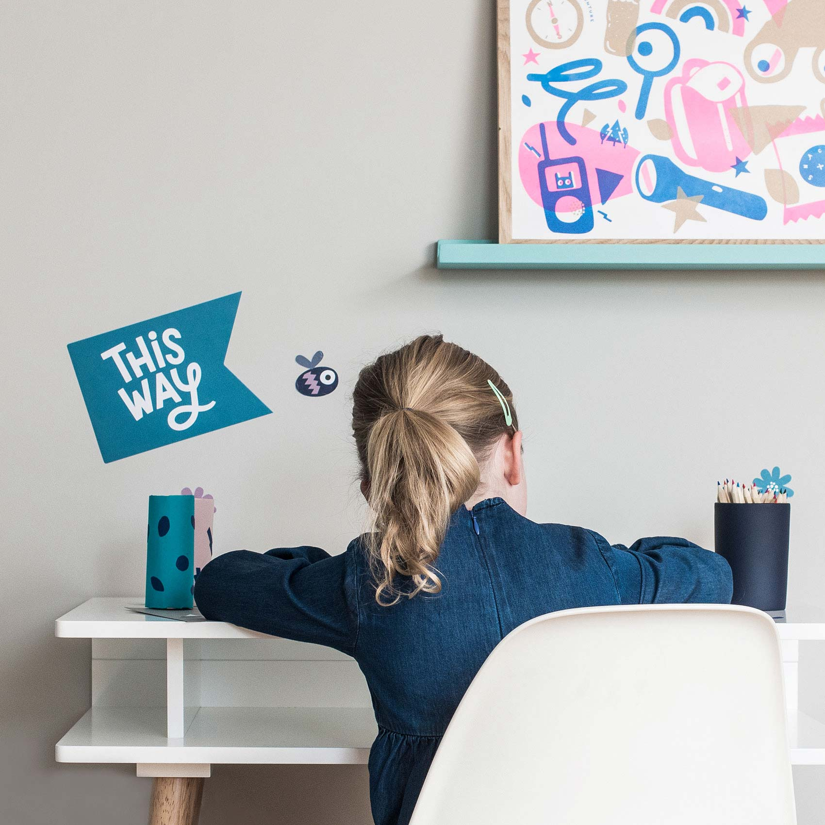 Young girl in Blue dress, sitting at a desk on a white chair. Adventure kit poster sits on a Green picture shelf, as well as a this way wall sticker on the wall.