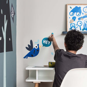 Young boy with back to camera sitting at desk applying Pea wall stickers to wall. Blue, Green and Bronze framed Adventure Kit poster print sits on a Navy shelf besides the young boy.