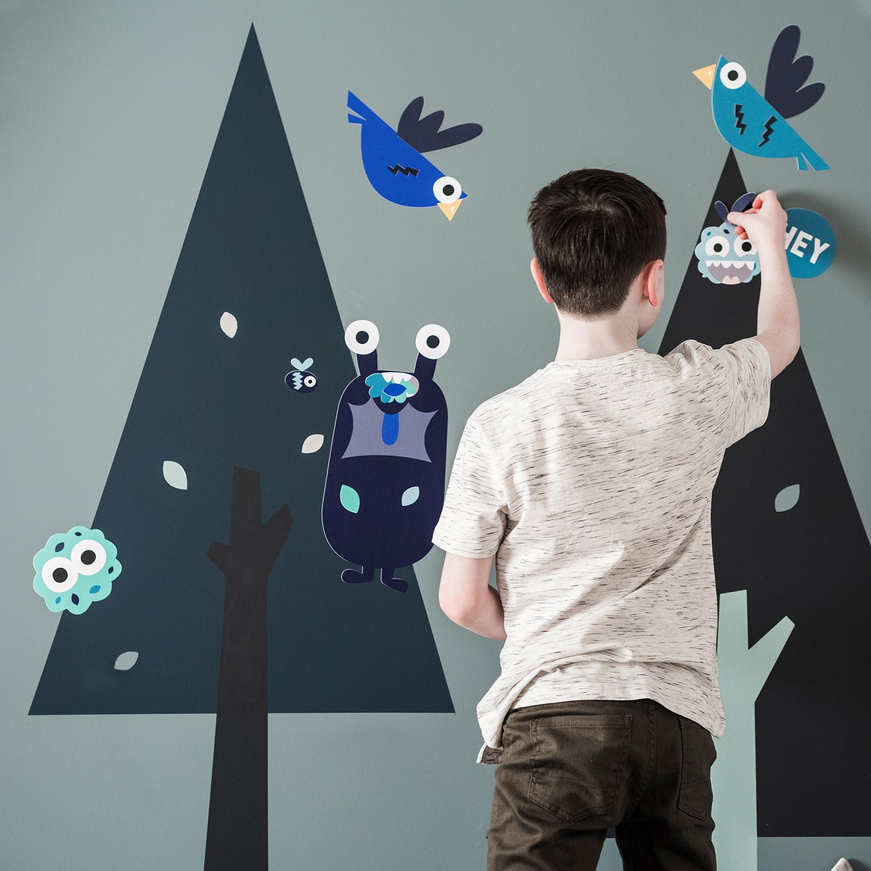 Young boy applying Treetops wall stickers to a wall painted in De Nimes Blue by Farrow and Ball alongside two tree applied using wall stencils .