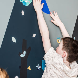 Young boy reaching up and applying a Blue bird wall sticker from Pea to a painted tree wall stencil.
