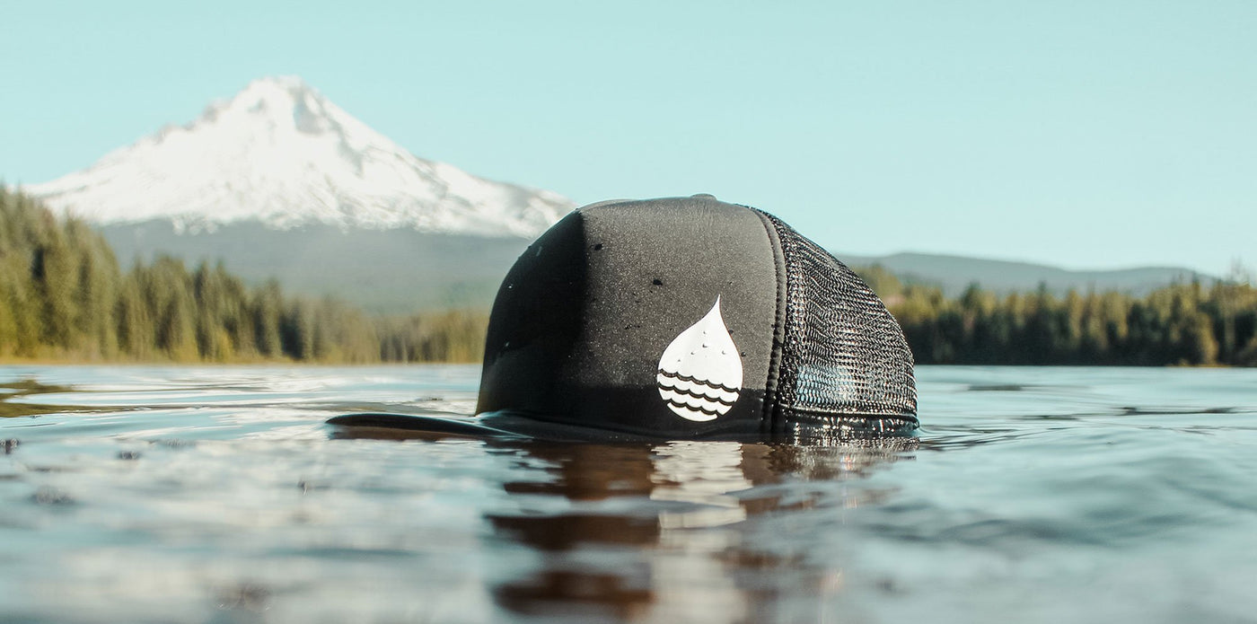 The BUOY WEAR black floating trucker hat in the lake with a view of Mount Hood, Oregon in the background.
