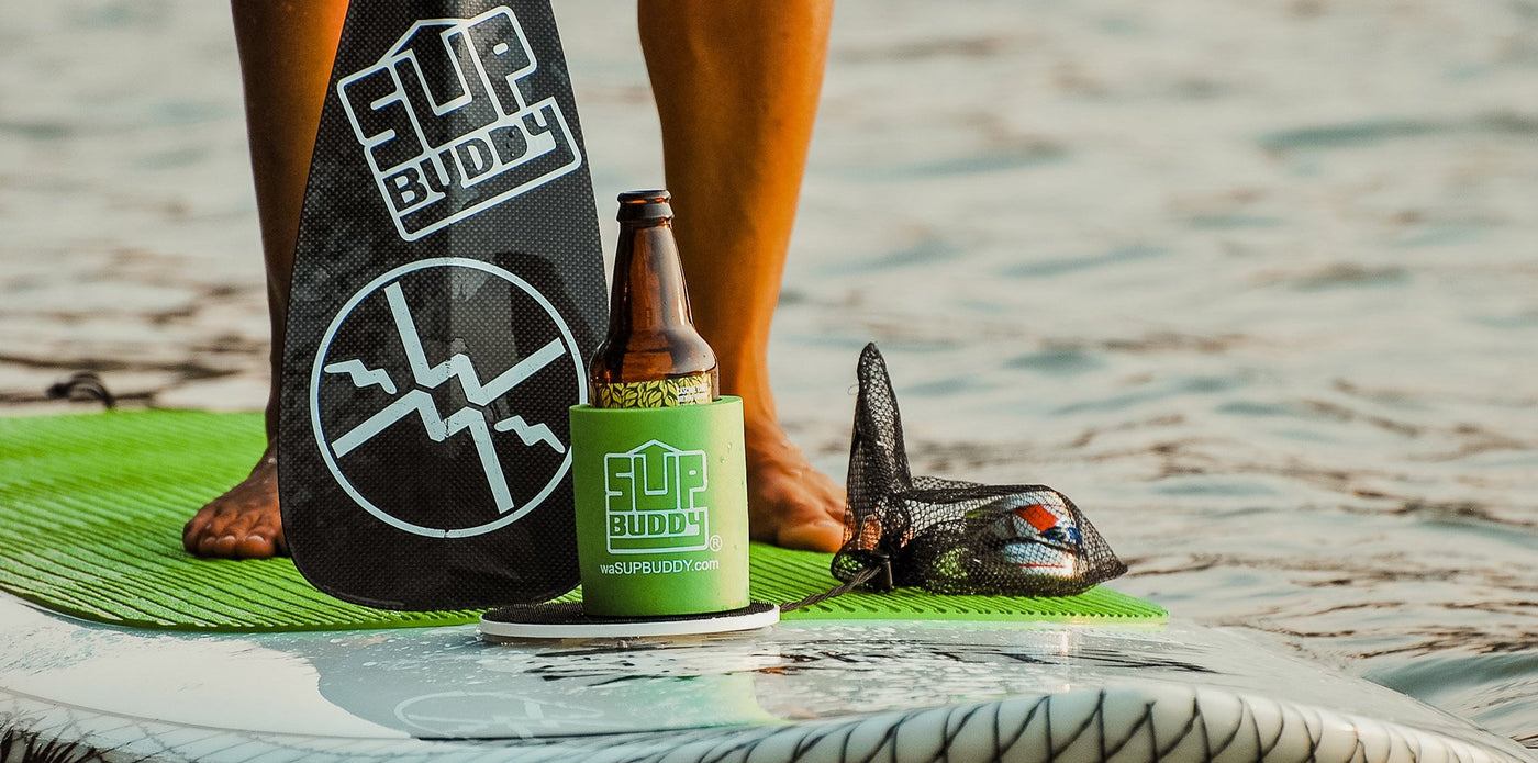 A zoomed in photo of a SUPBUDDY Koozie on a stand up paddleboard on the beach.