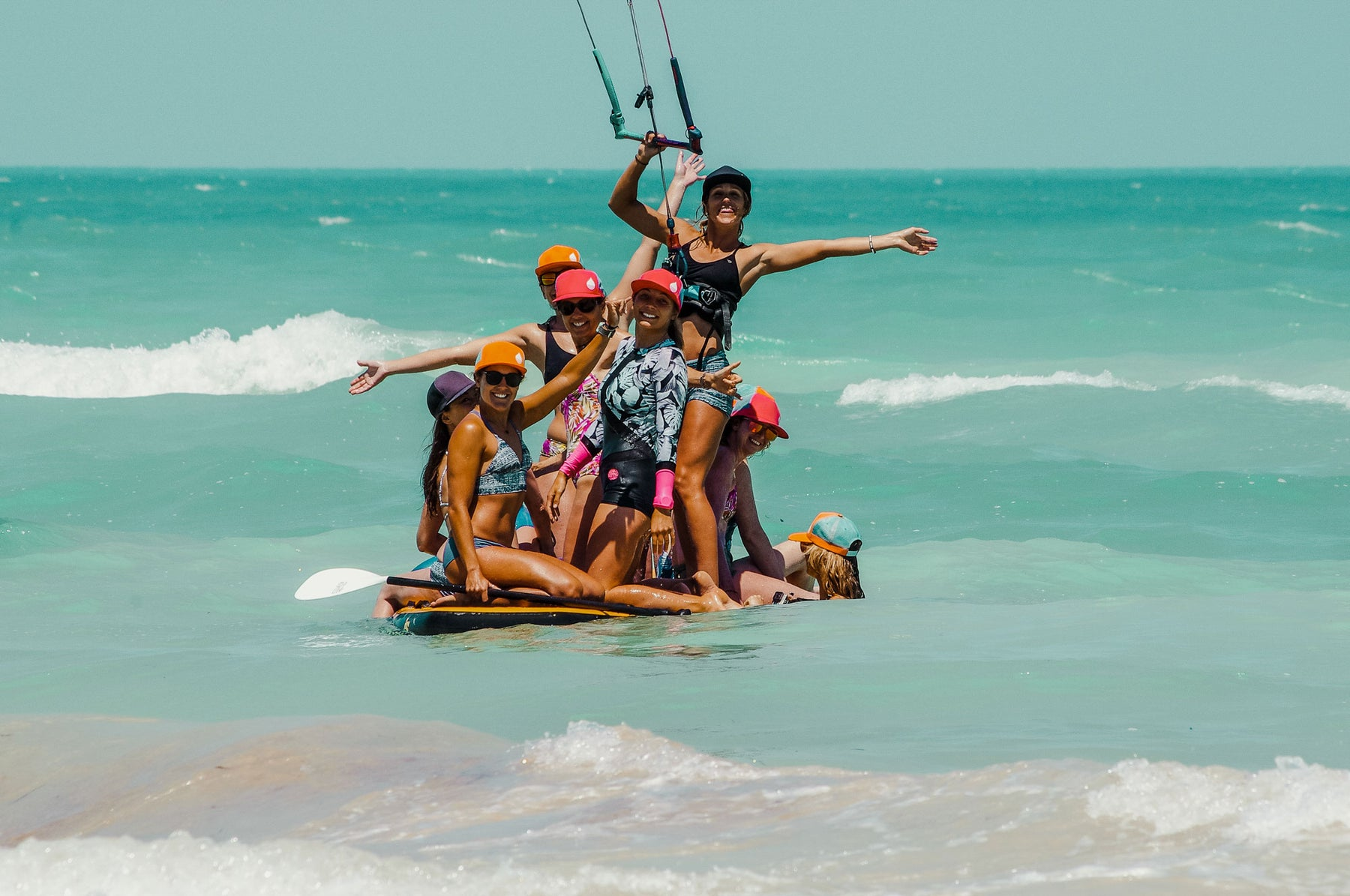 Women on a SUP in the emerald waters of Mexico, all wearing a BUOY WEAR floating hat.