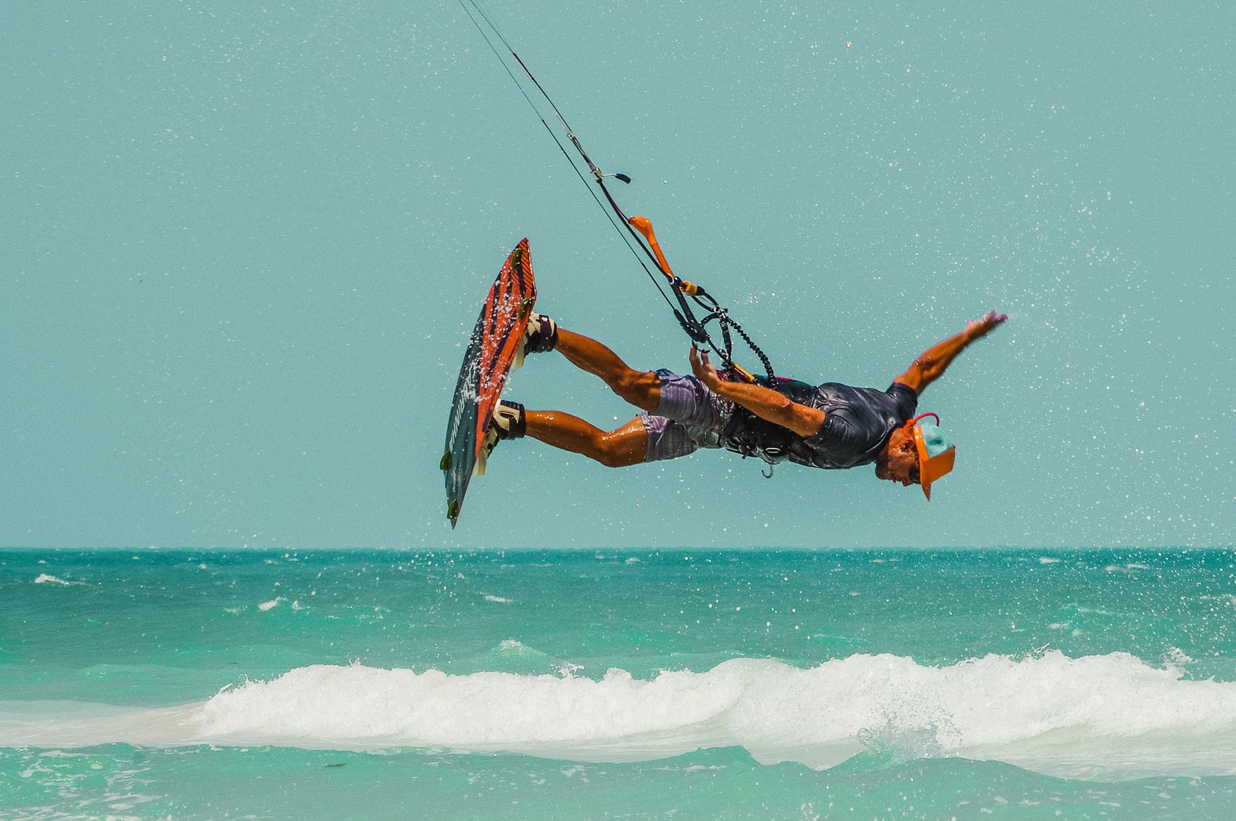BUOY WEAR founder John Ruffing out in the ocean kiteboarding and wearing an orange floating, waterproof hat.