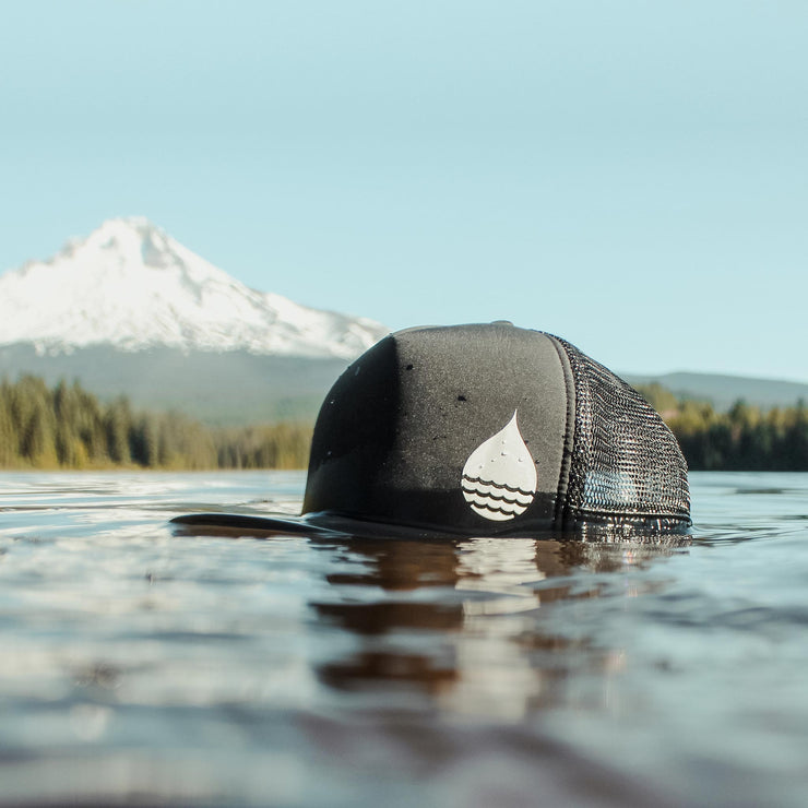 Black Floating, Waterproof Trucker Hat with Snapback in the lake with a view of Mount Hood in the background - BUOY WEAR