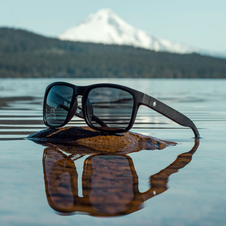 Black Matte Polarized Floating Sunglasses displayed at Timothy Lake, Oregon with Mount Hood in the background - BUOY WEAR
